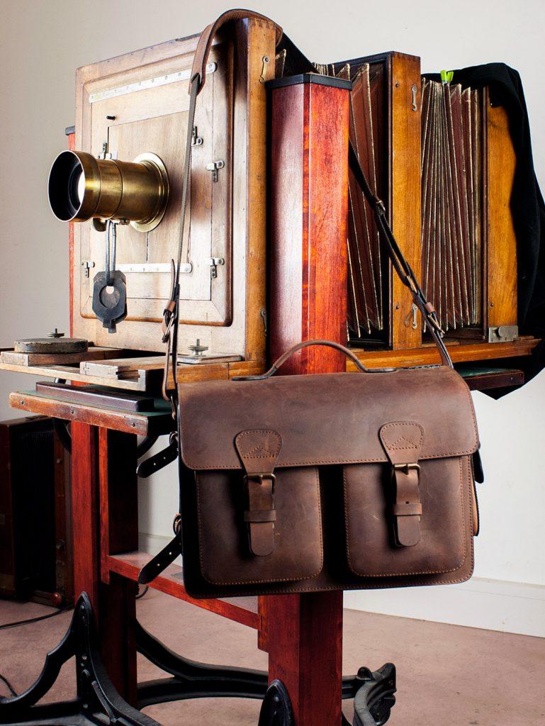 Cartable vintage en cuir marron avec ancien appareil photo.