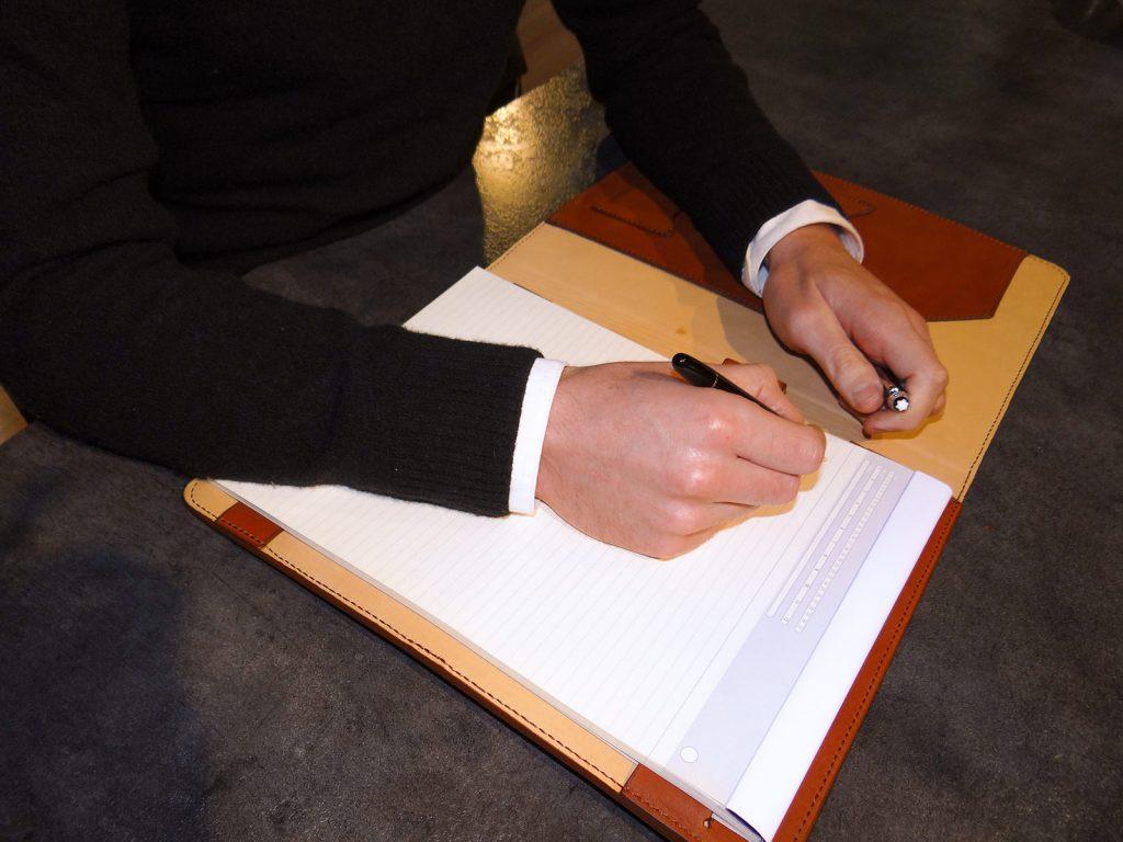 Écriture dans le conférencier en cuir.
