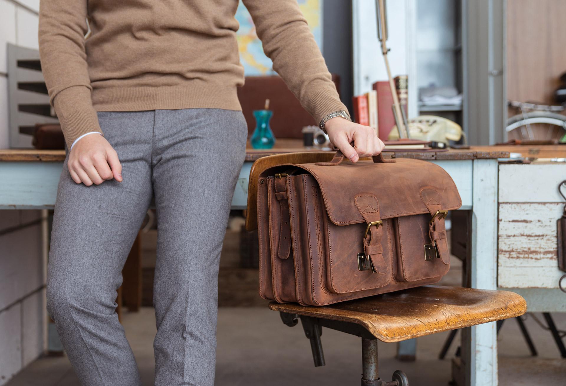 Enseignant avec cartable en cuir marron.